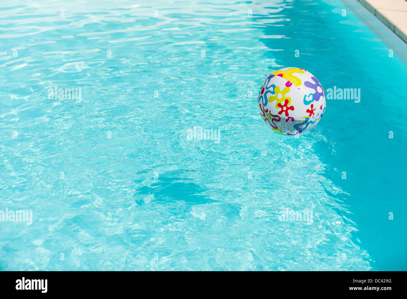 Pool Water With Beach Ball colorful beach ball floating on water of swimming pool stock photo