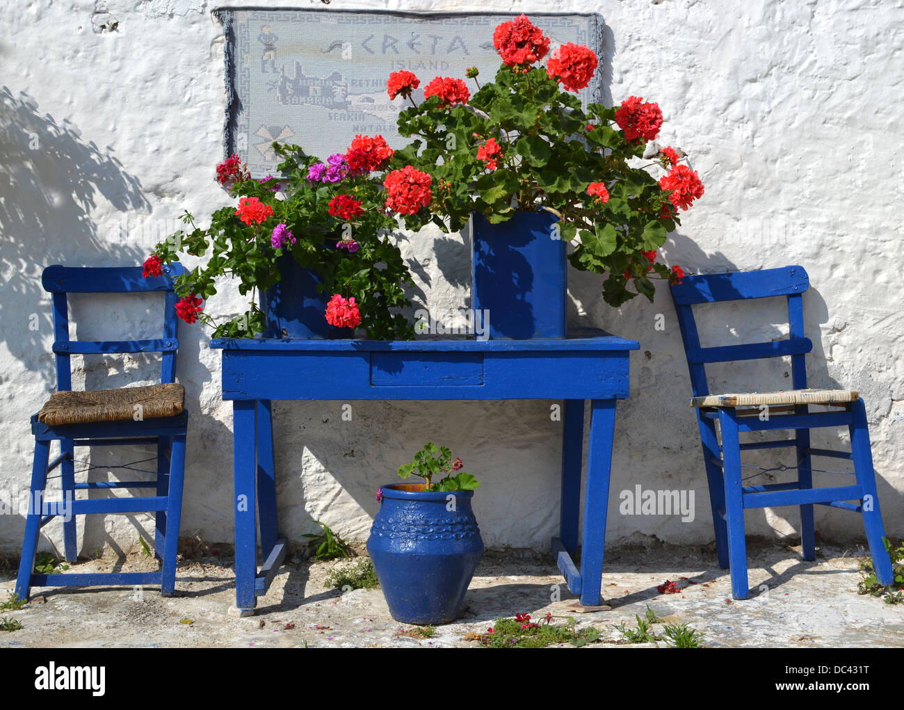 typical greek courtyard with blue flower pots in piskopiano on