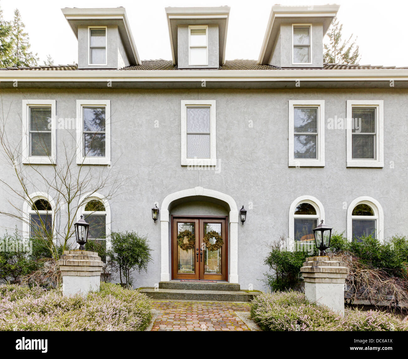 Home Exterior Of Large Grey Classic House With Many Narrow Windows