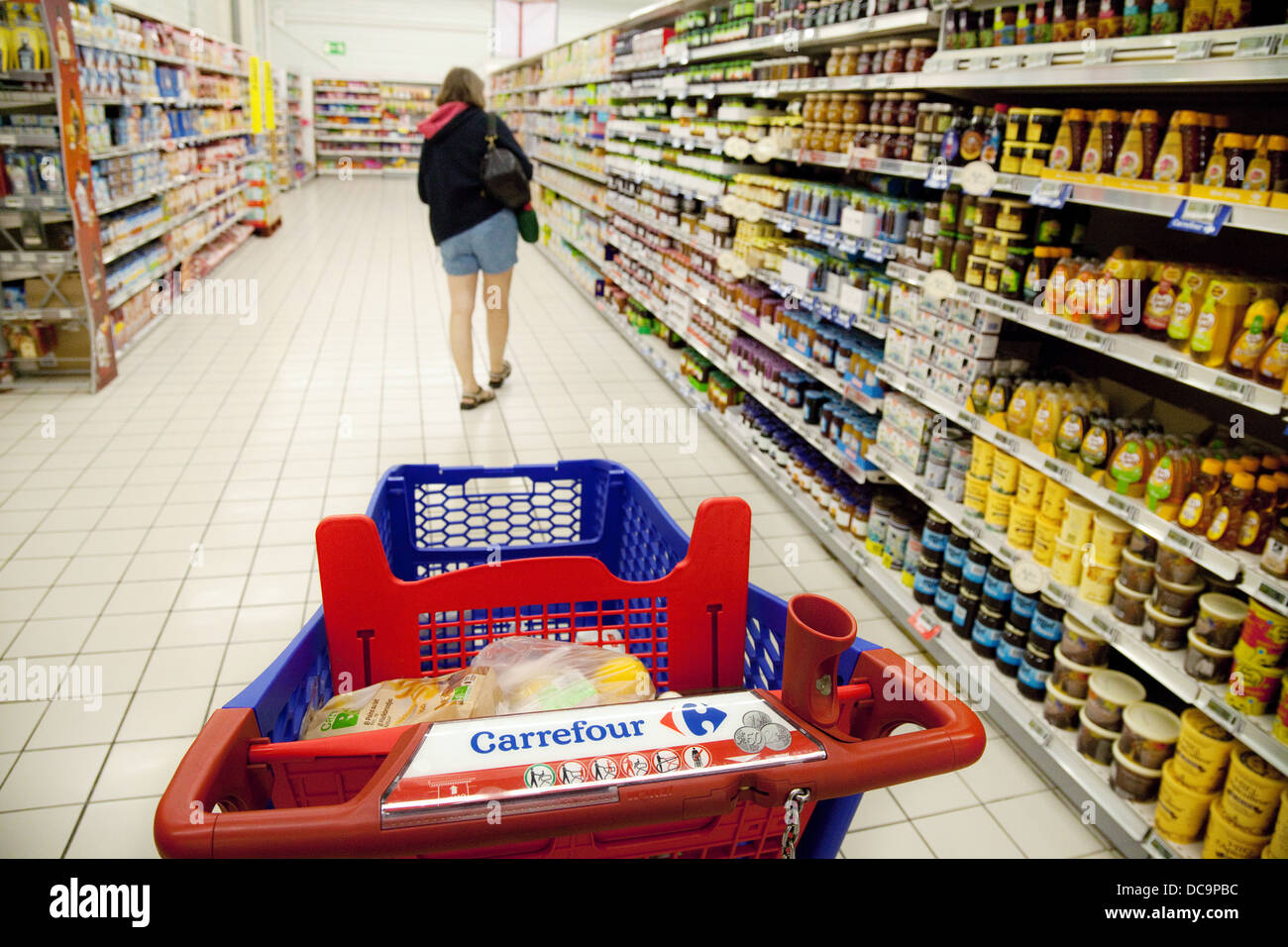 a woman shopping for food in the aisle of a carrefour french stock photo royalty free image. Black Bedroom Furniture Sets. Home Design Ideas