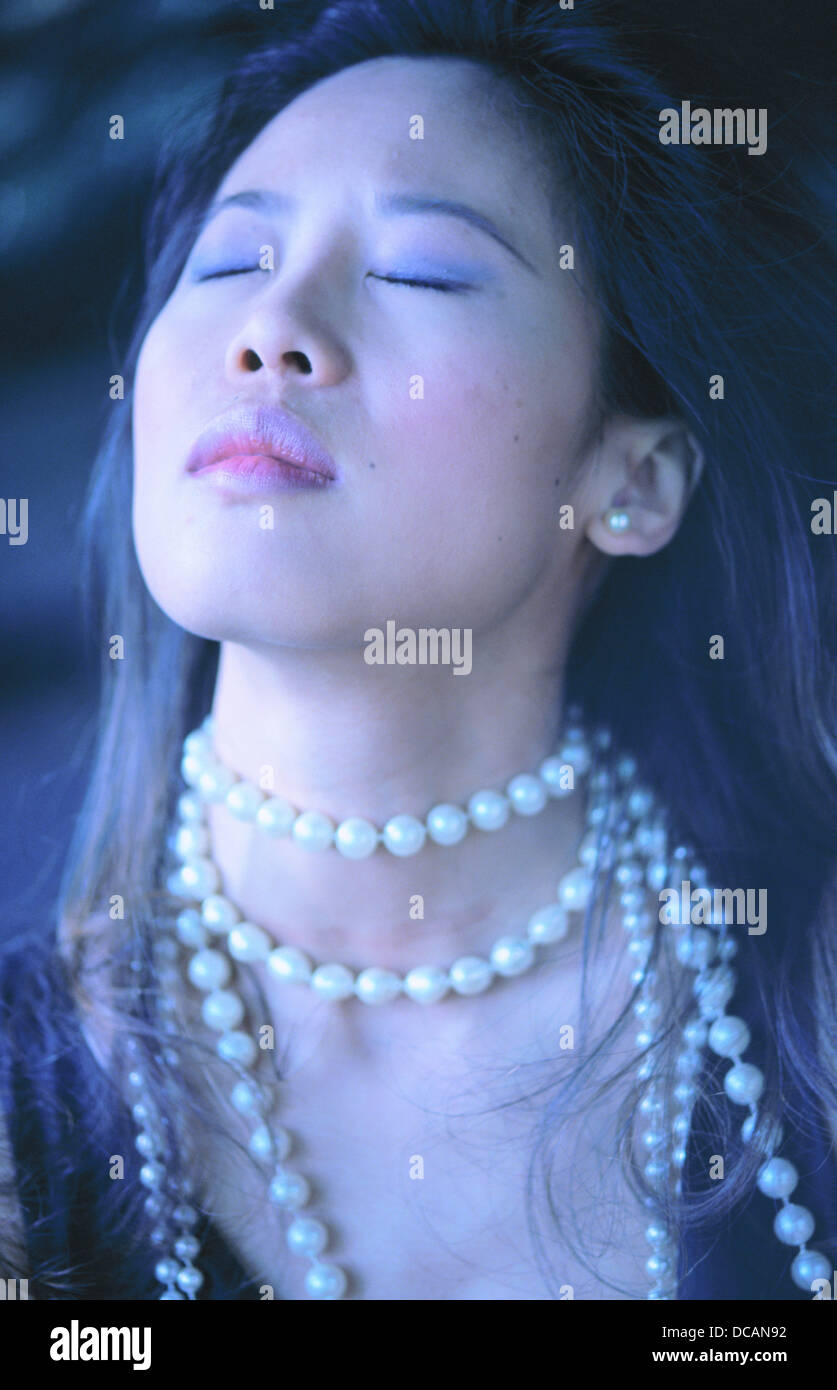 Portrait Of A Glamorous Young Chinese Woman, Face Tilted Up To The Left  With Eyes Closed And Wearing A Long Pearl Necklace
