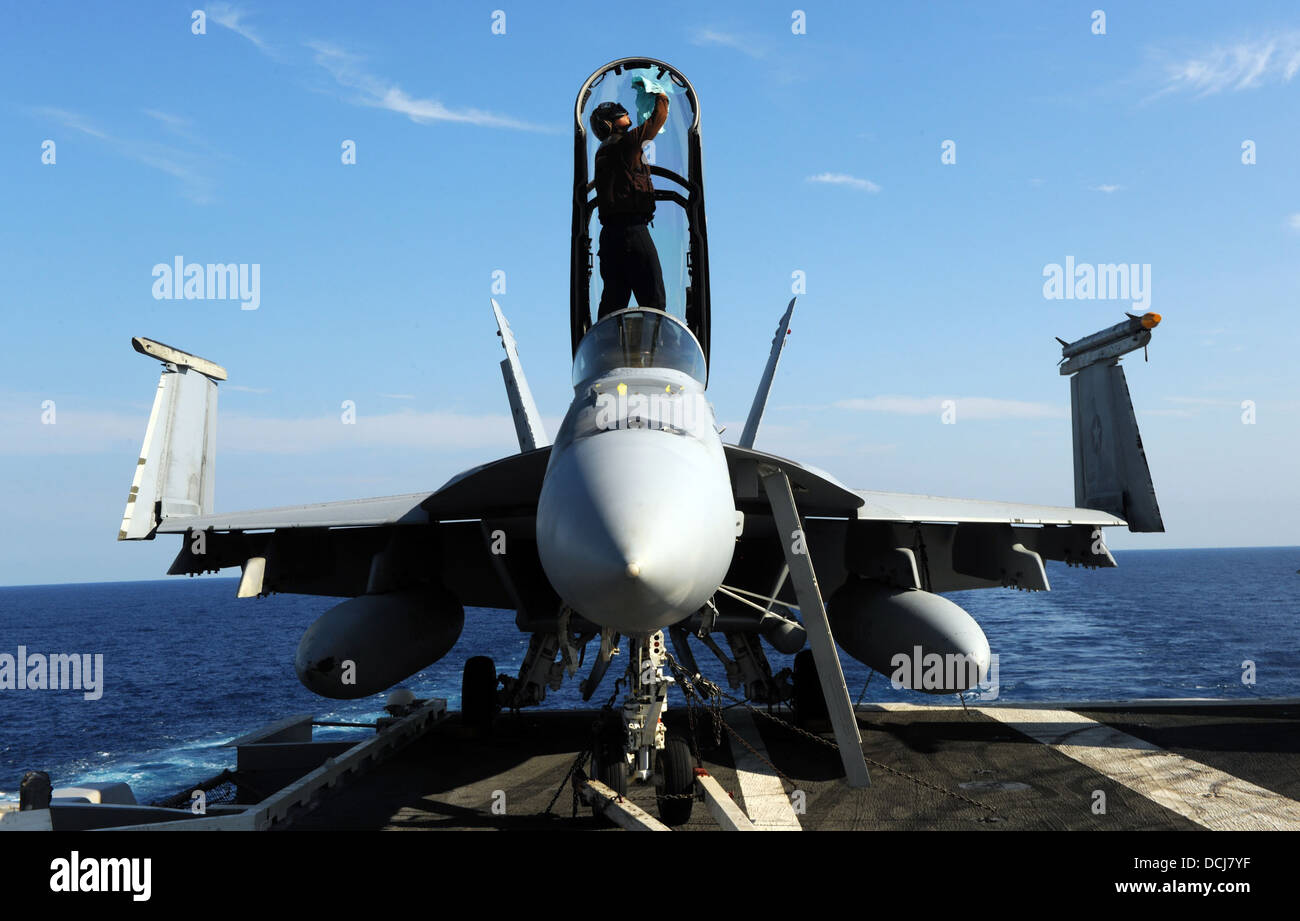 cleans the canopy of an F/A-18F Super Hornet assigned to the Fighting Black Lions of Strike Fighter Squadron (VFA) 213 on the flight deck of the aircraft ... & cleans the canopy of an F/A-18F Super Hornet assigned to the ...