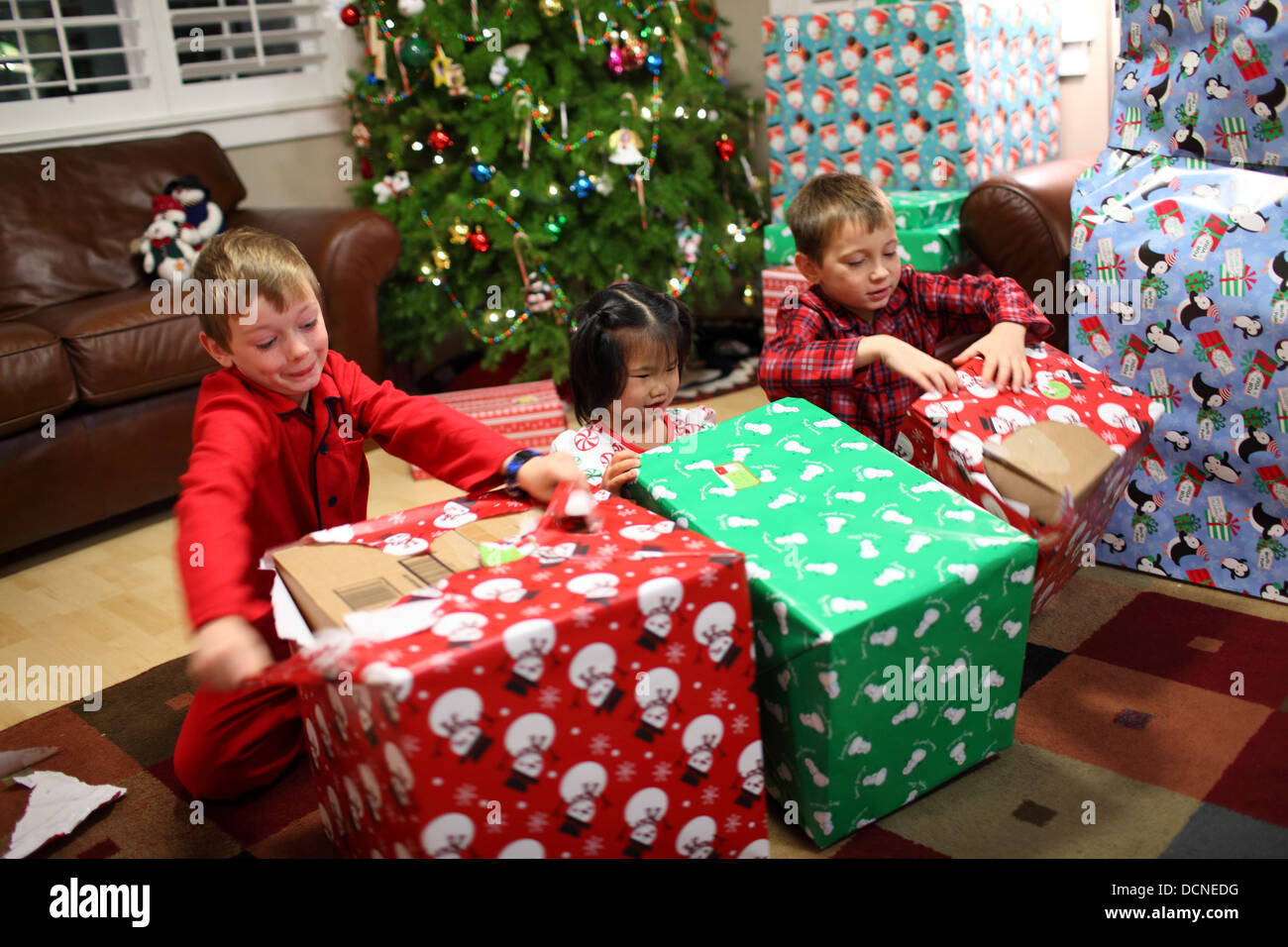 Three Kids Opening Christmas Presents Stock Photos & Three Kids ...