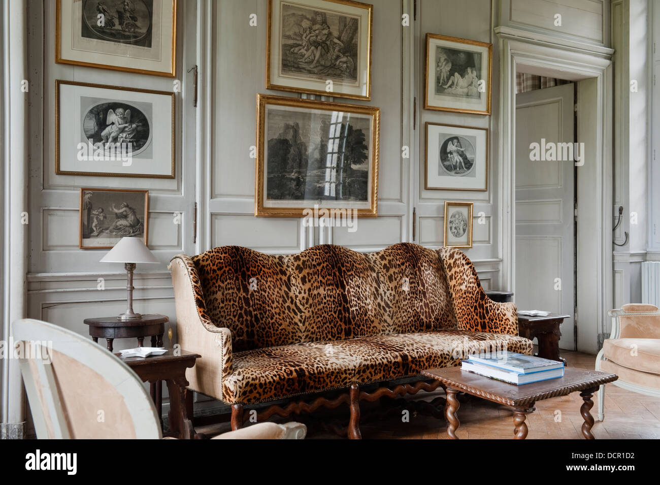 Antique French sofa upholstered in leopard print fabric in living room with  wooden wall panelingAntique French sofa upholstered in leopard print fabric in living  . Animal Print Living Room. Home Design Ideas