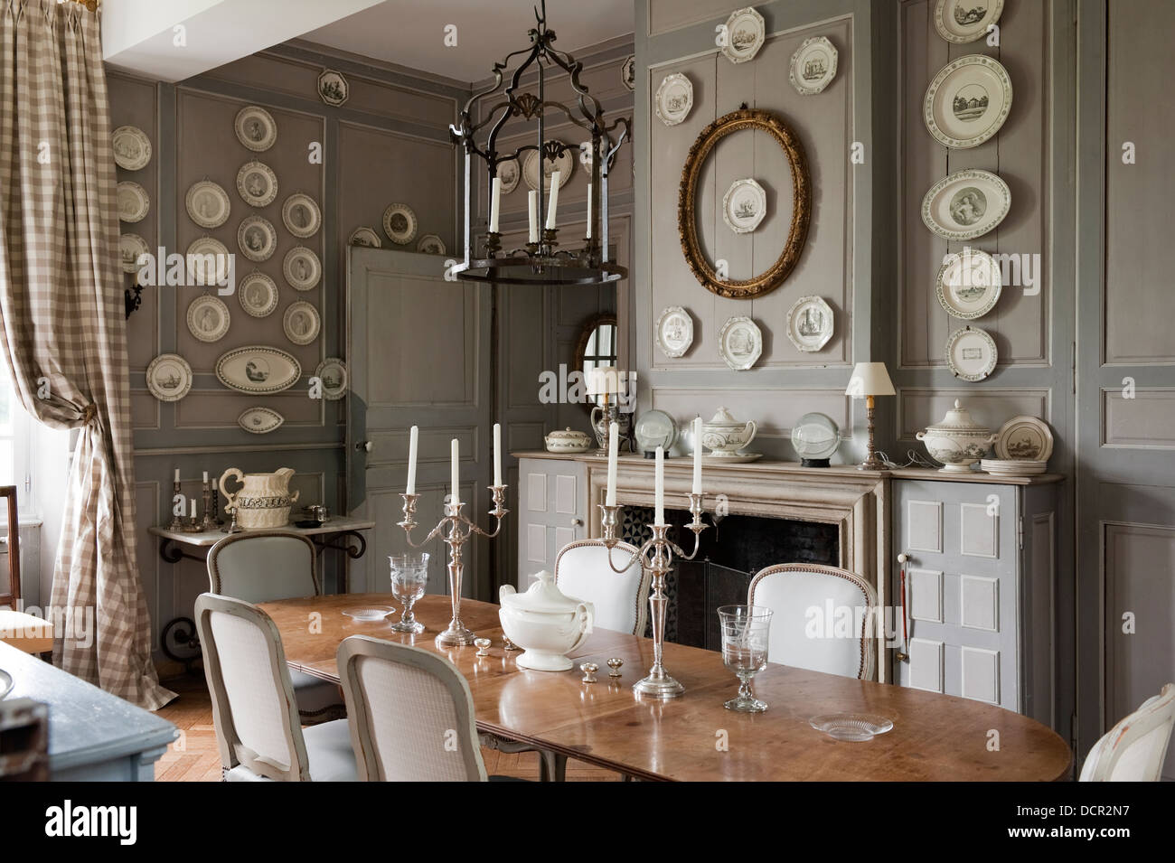 elegant dining rooms. French antique chairs and table in elegant dining room with wood wall  panelling decorative plates