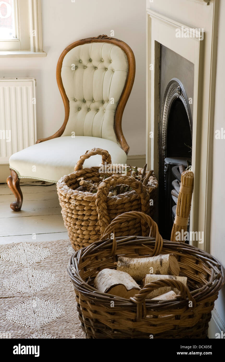low chair and log baskets with original fireplace of country house