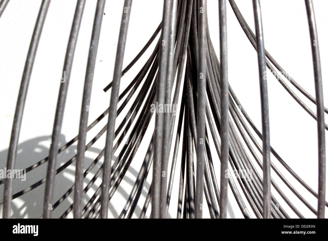 An abstract studio shot of a coil of unravelling thick metal wire ...