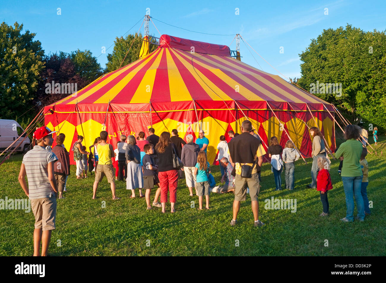Striped yellow and red circus tent with crowd