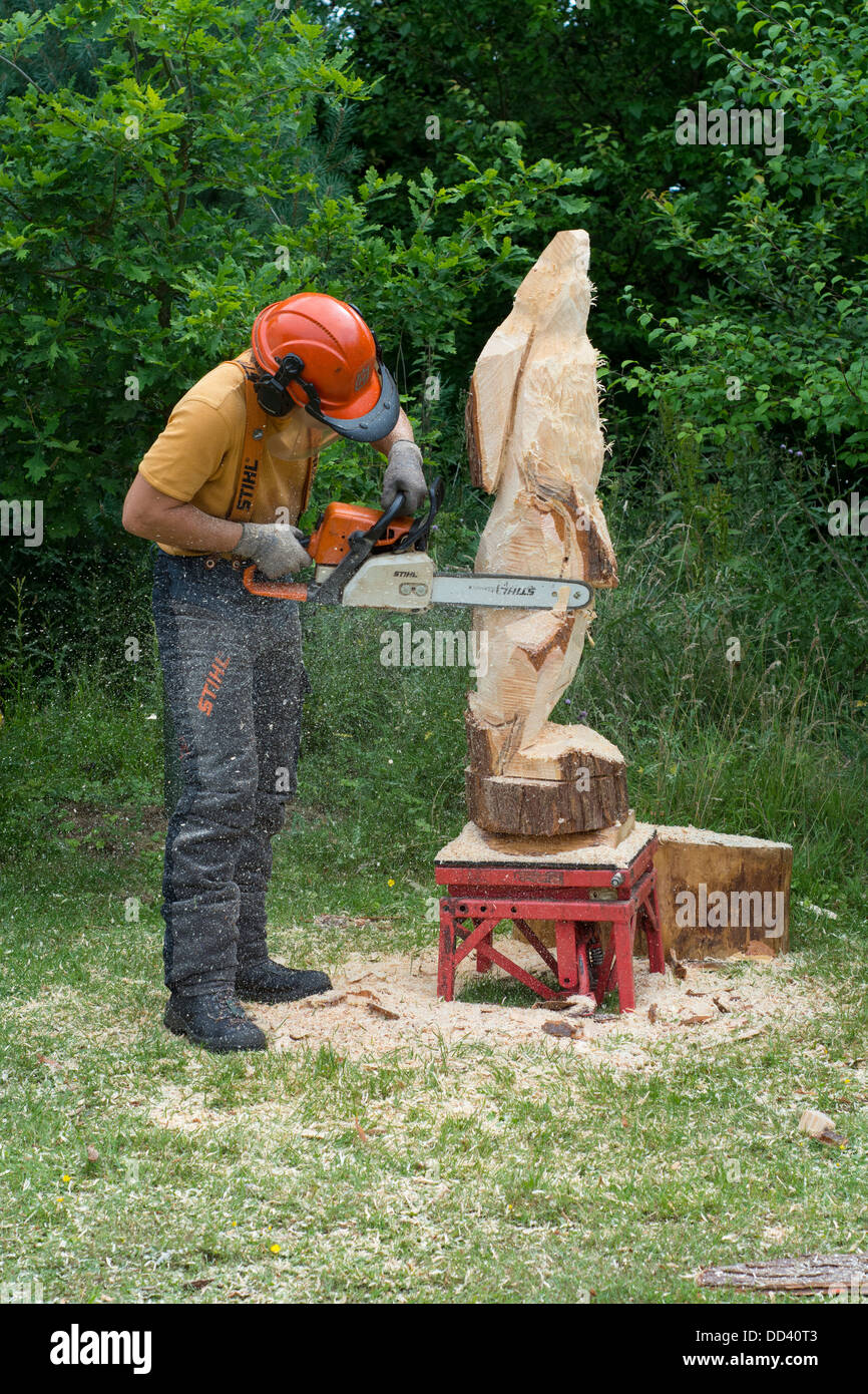 Chainsaw carving man hare form solid tree trunk