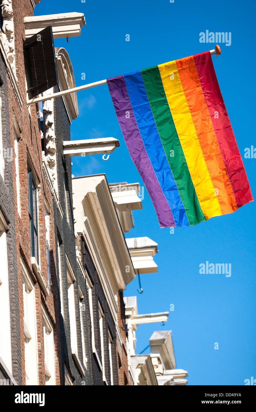 rainbow colored flag flies from a typical row of canal houses in