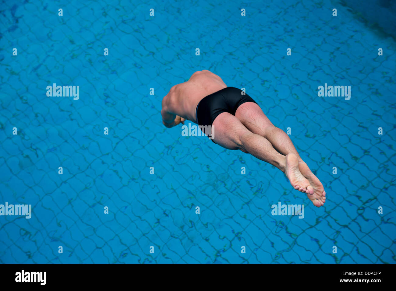 Public Swimming Pools With Diving Boards man jumping from diving board at public swimming pool stock photo