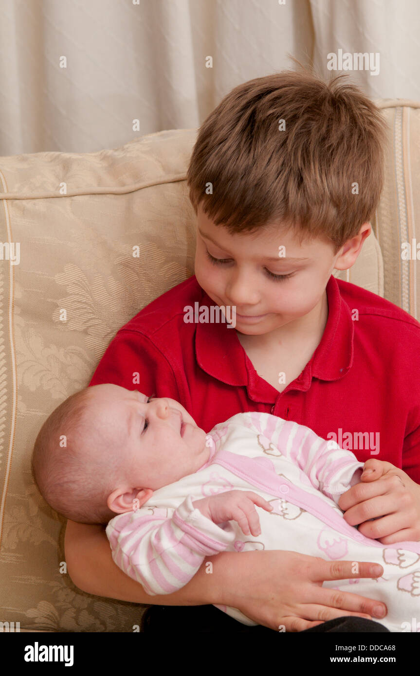 8 Year Boy Bedroom Design: Eight Year Old Boy Holding His Baby Sister Stock Photo