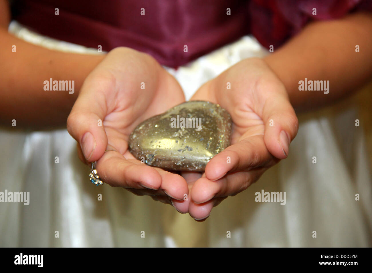 Young girl\'s open hands holding out stone cut in the shape of a ...