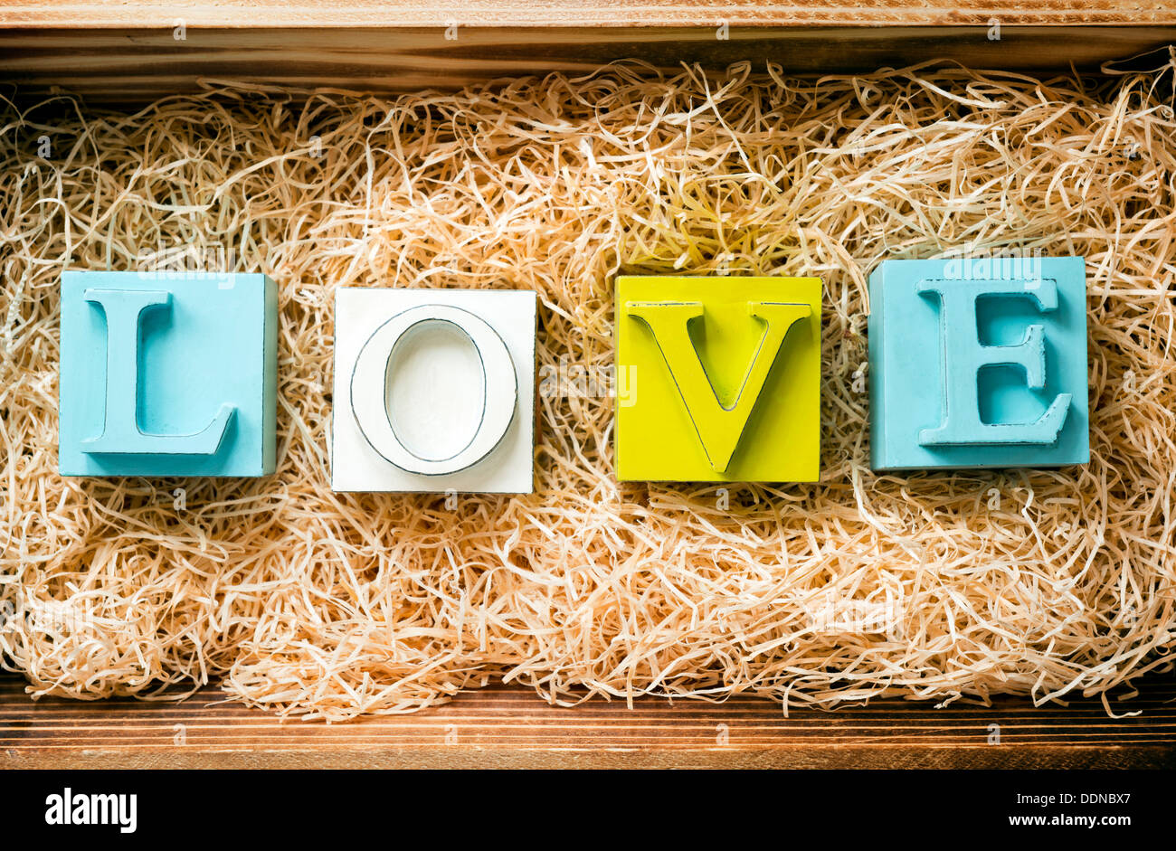 The Word Love Spelled Out In Big Block Letters A Wooden Gift Box Filled With Raffia