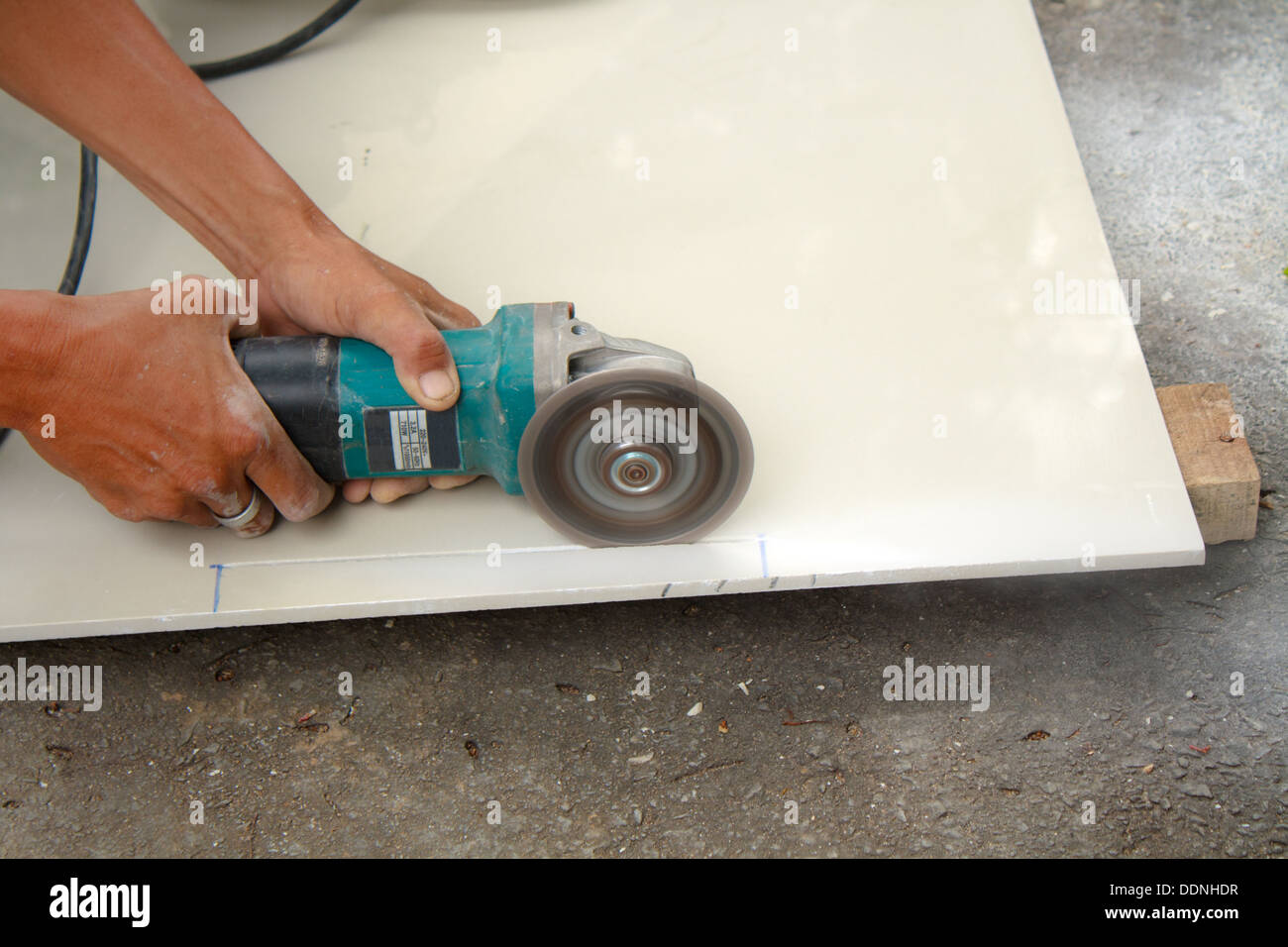 Workers are using tools for cutting tile stock photo royalty free workers are using tools for cutting tile dailygadgetfo Images