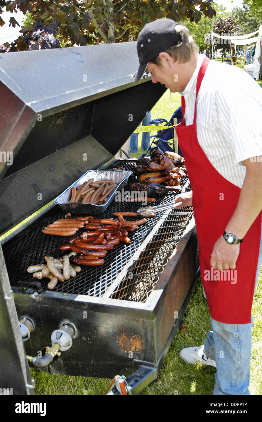 Male prepares turkey legs, hamburgers, and hot dogs on a large ...