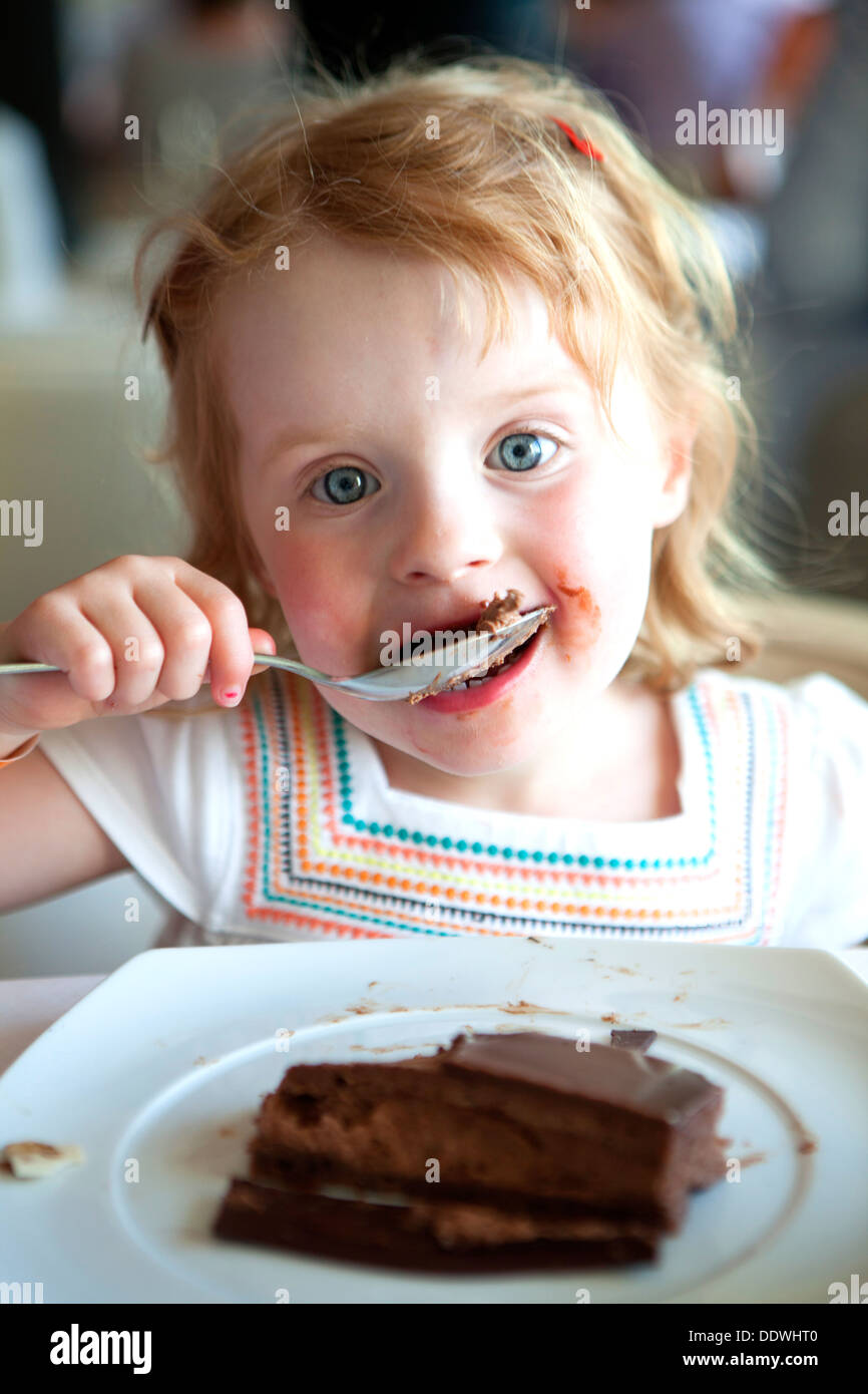 4 year old girl eating chocolate cake with a spoon Stock ...
