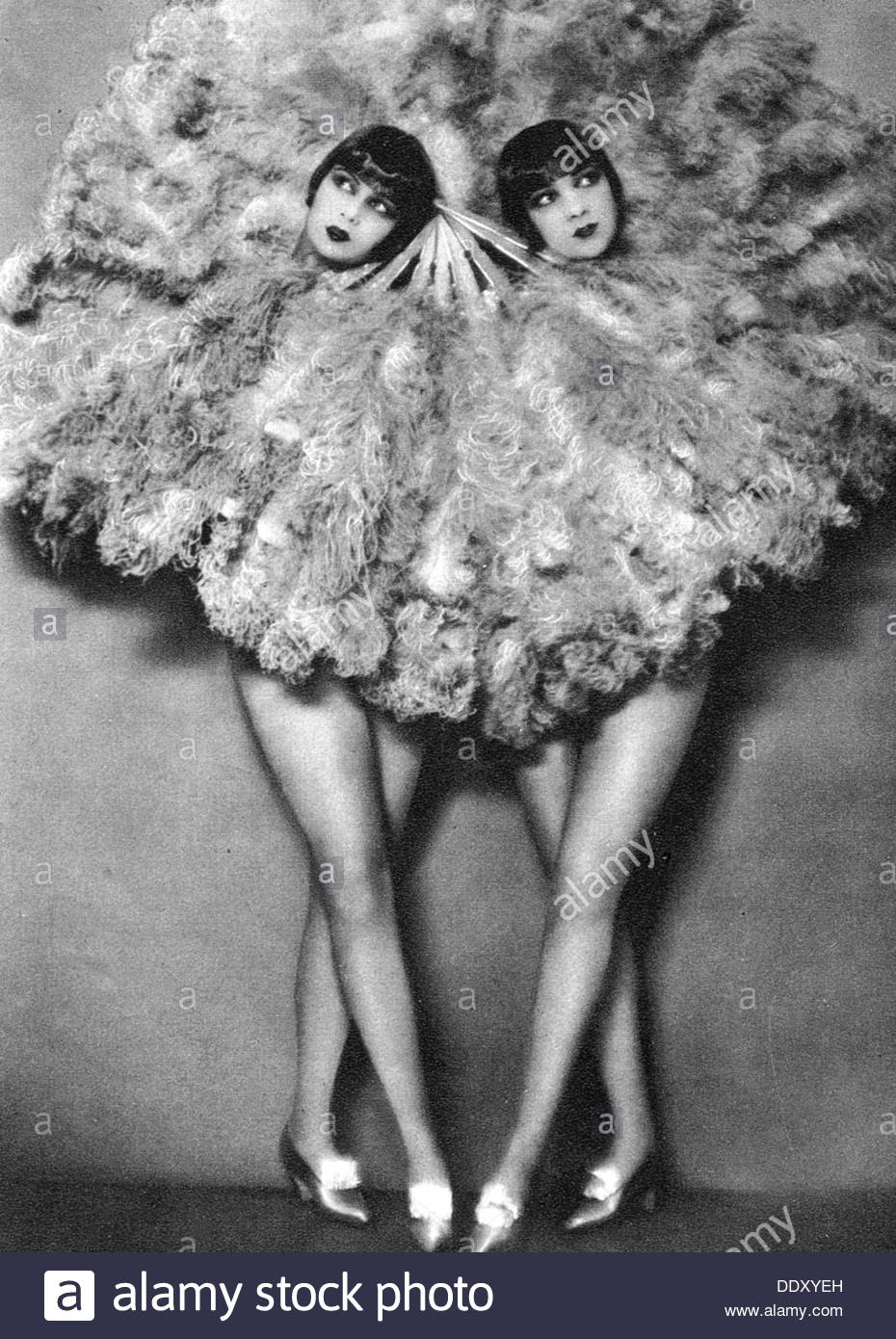 A pair of dancing girls, shielded by large feather fans, 1920s ...