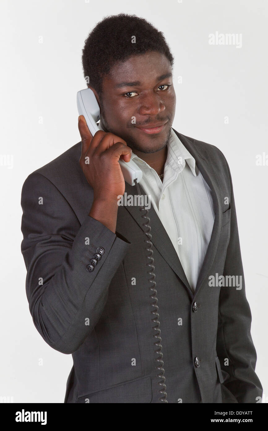 Young black man in a suit making a phone call in an office ...