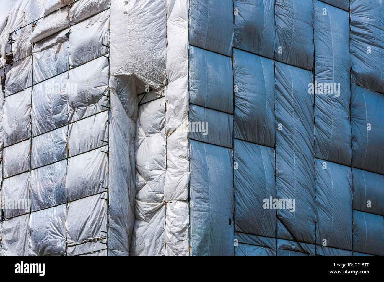 scaffolding surrounded by a silver plastic tarp protection from falling components frankfurt am main hesse germany