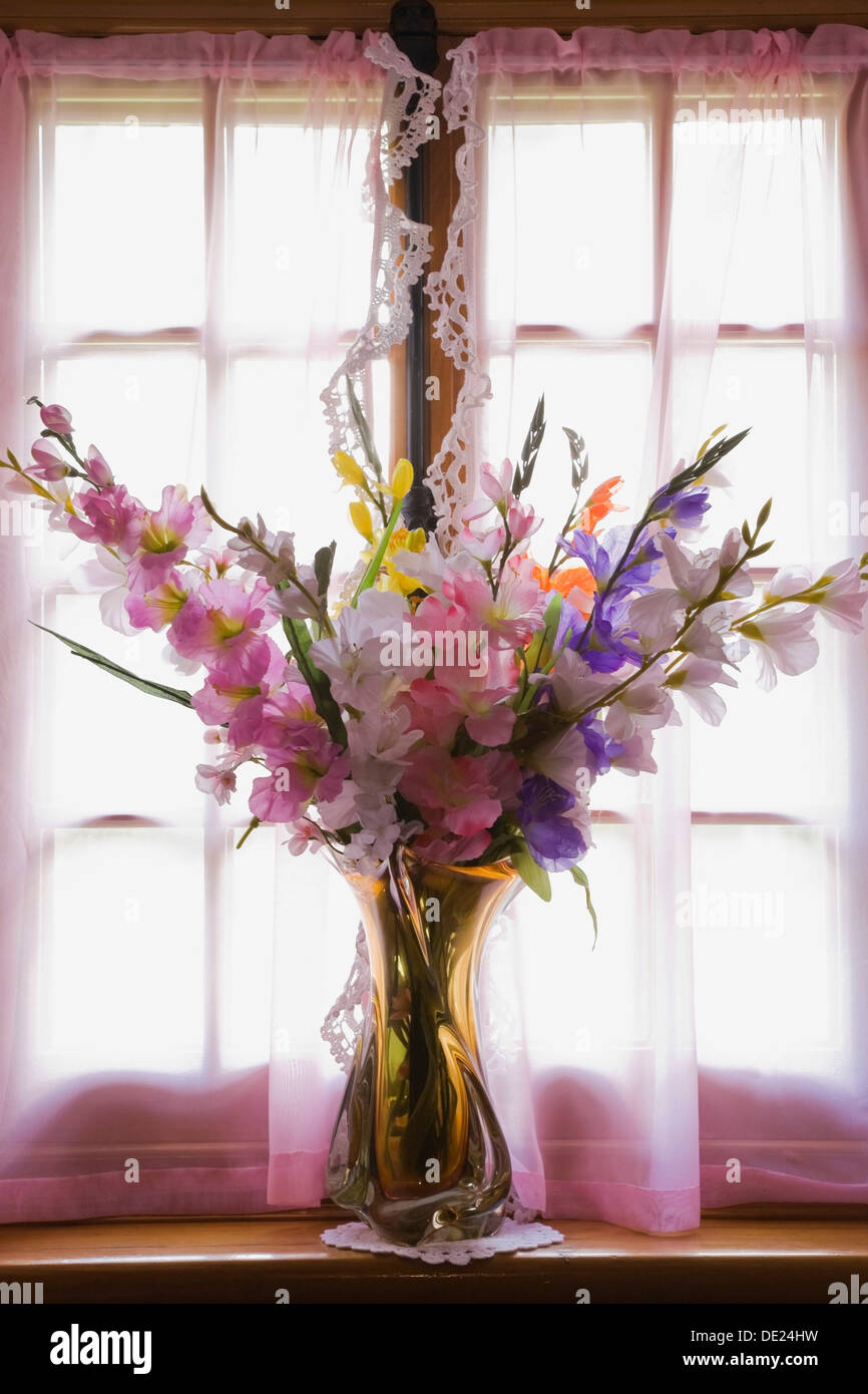 Glass vase with silk flowers on the window sill of an old stock glass vase with silk flowers on the window sill of an old reconstructed 1983 canadiana cottage style residential log home reviewsmspy