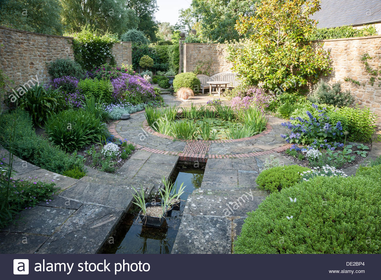 Walled garden with circular water lily pond fringed with for Circular garden ponds