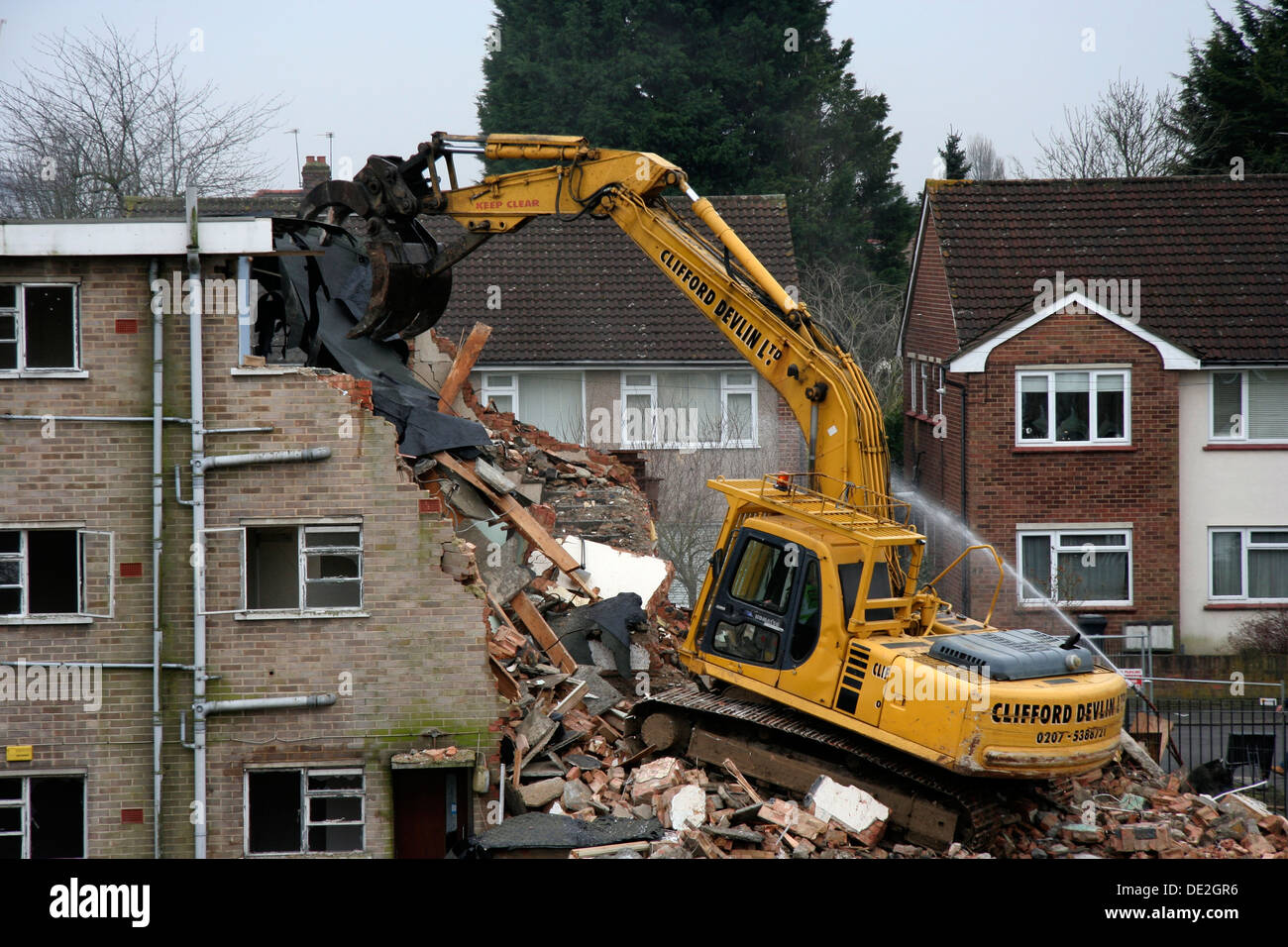 the demolition of a small block of flats using an excavator water