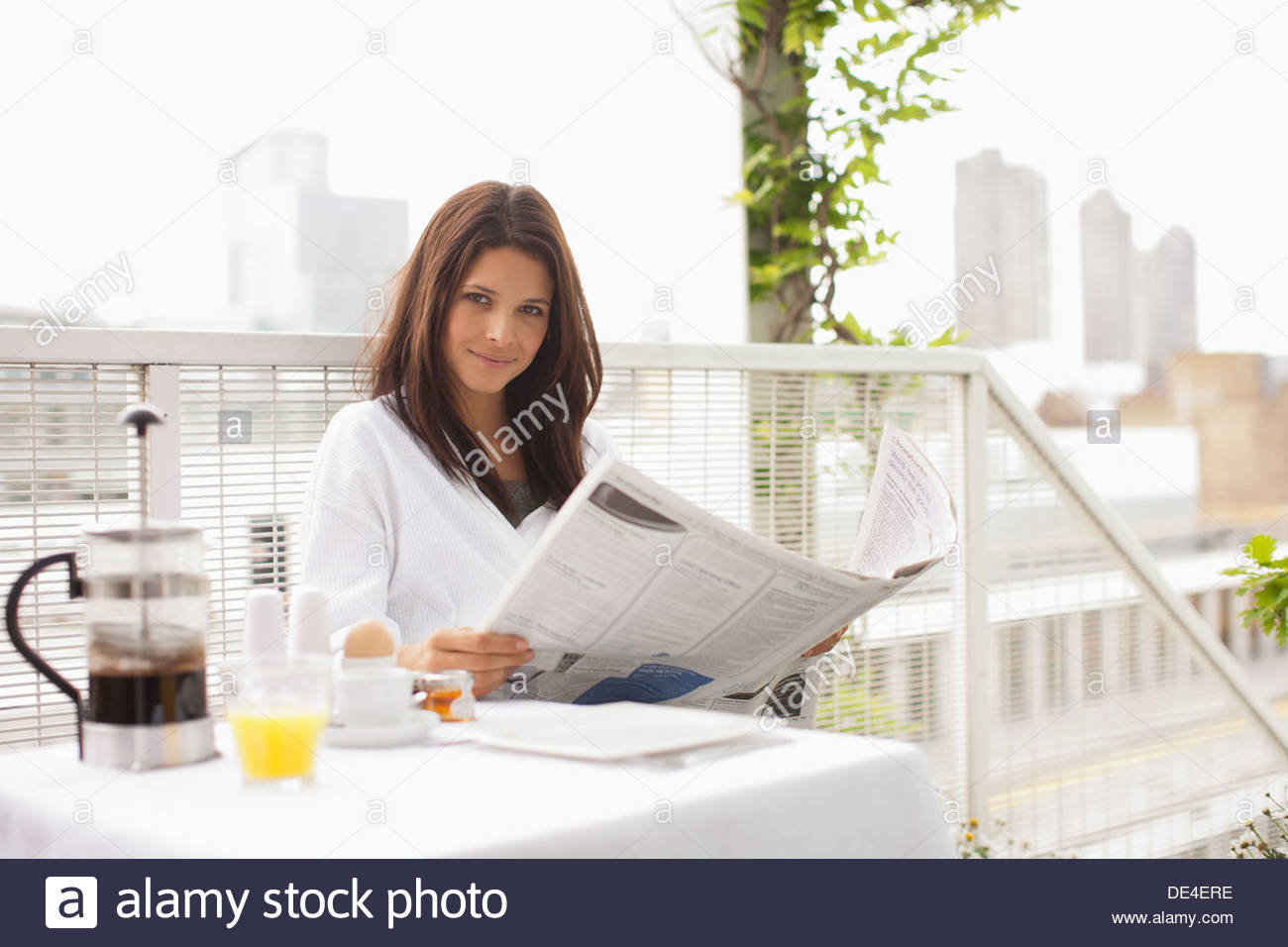 Woman reading newspaper and having breakfast on balcony ...