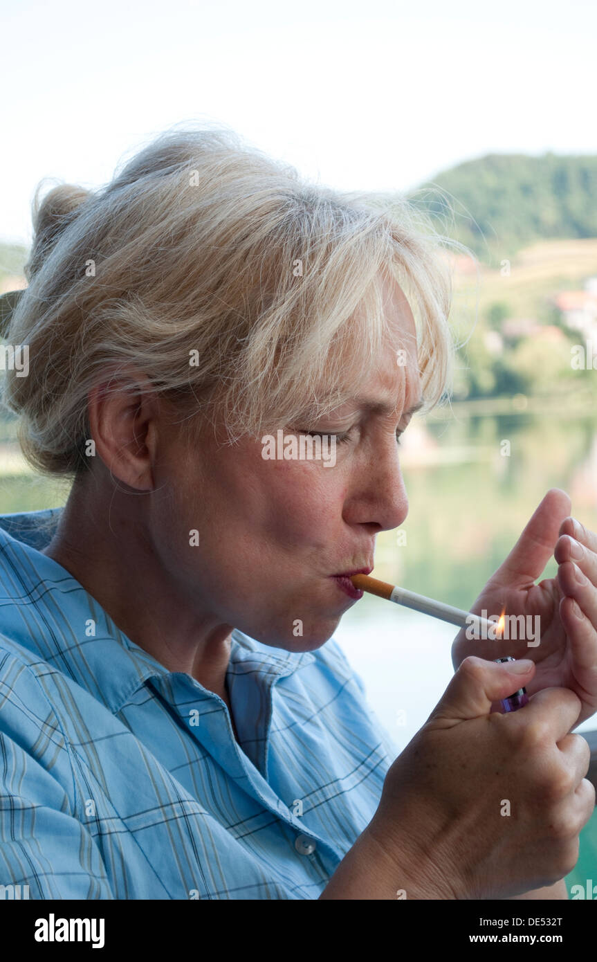 Middle aged woman lighting up a cigarette  sc 1 st  Alamy & Middle aged woman lighting up a cigarette Stock Photo Royalty ... azcodes.com