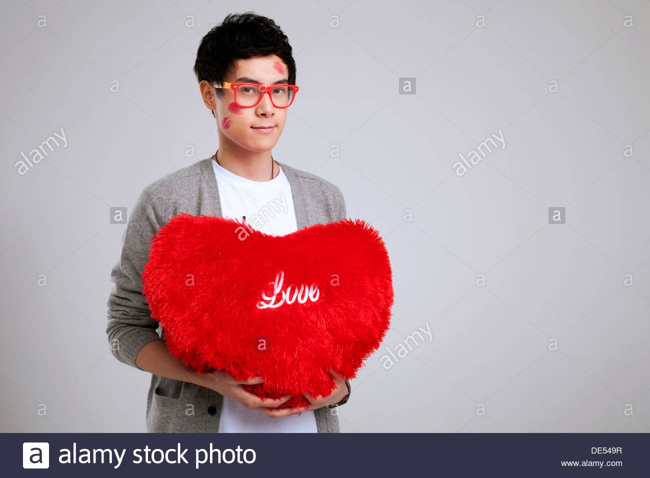 Man Shaped Pillow A Young Man Holding A Heart Shaped Pillow Stock Photo Royalty