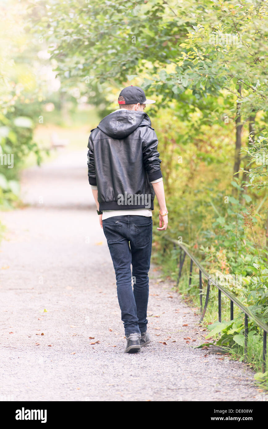 Young man walking away on footpath in a park Stock Photo