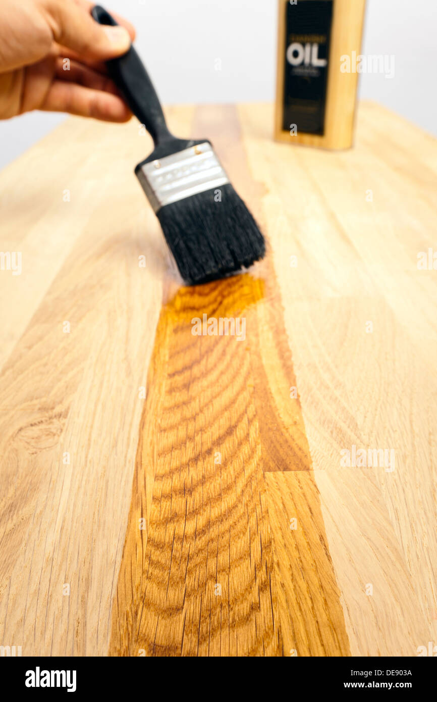 brushing a protective oil treatment onto a solid oak kitchen worktop selective focus on foreground wood