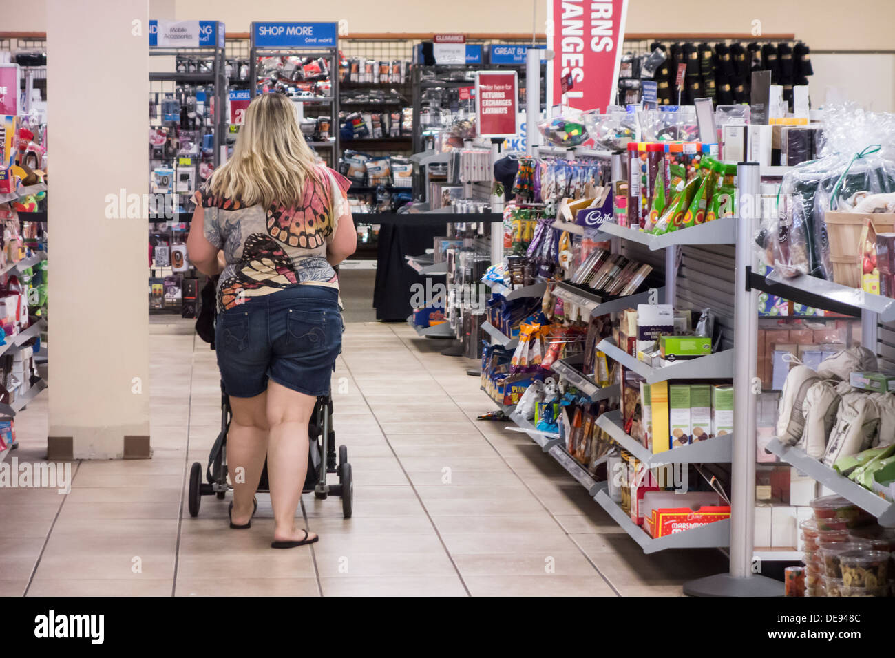 A Young, Obese Woman Shops In A Department Store While Pushing A ...