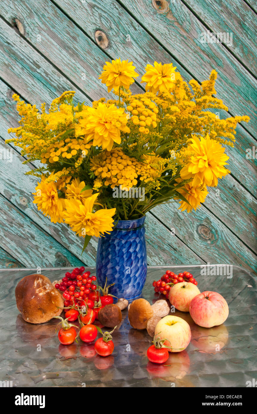 Yellow flowers bouquet in a blue vase with apples and rose hips yellow flowers bouquet in a blue vase with apples and rose hips izmirmasajfo Image collections