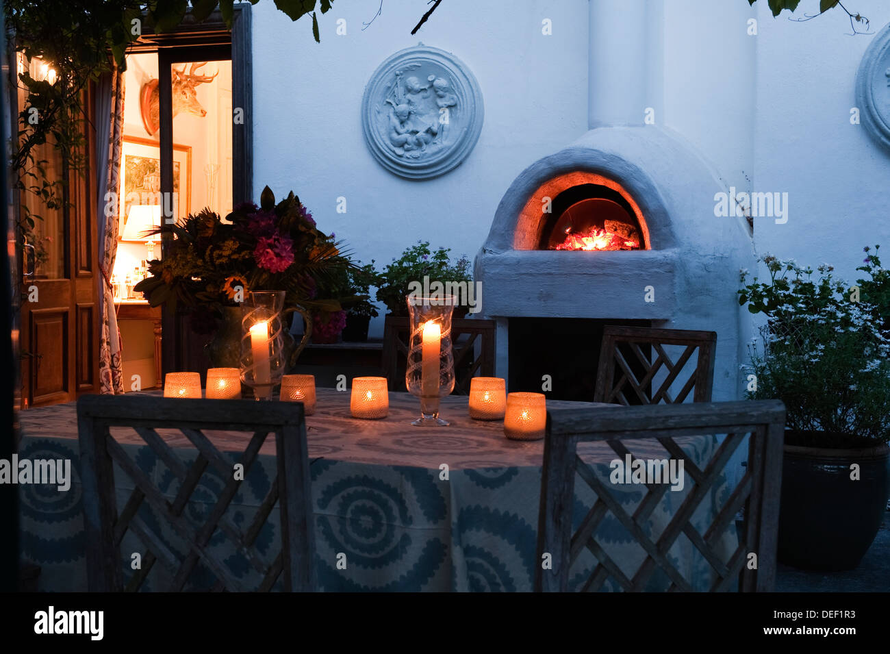 Lit Candles On Patio Table Of Country Residence