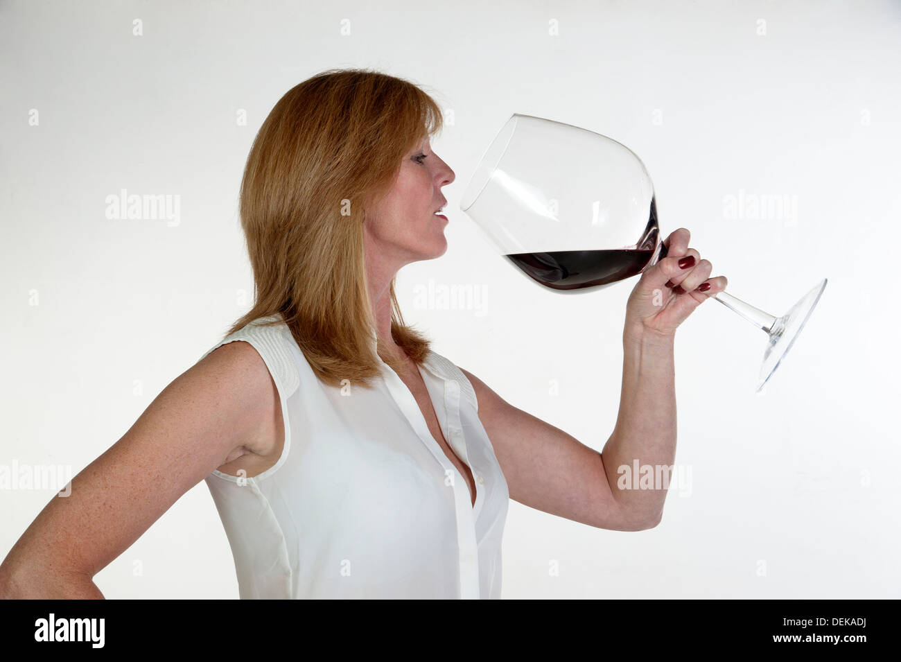 Woman tasting from a very large glass of red wine stock for Large red wine glass
