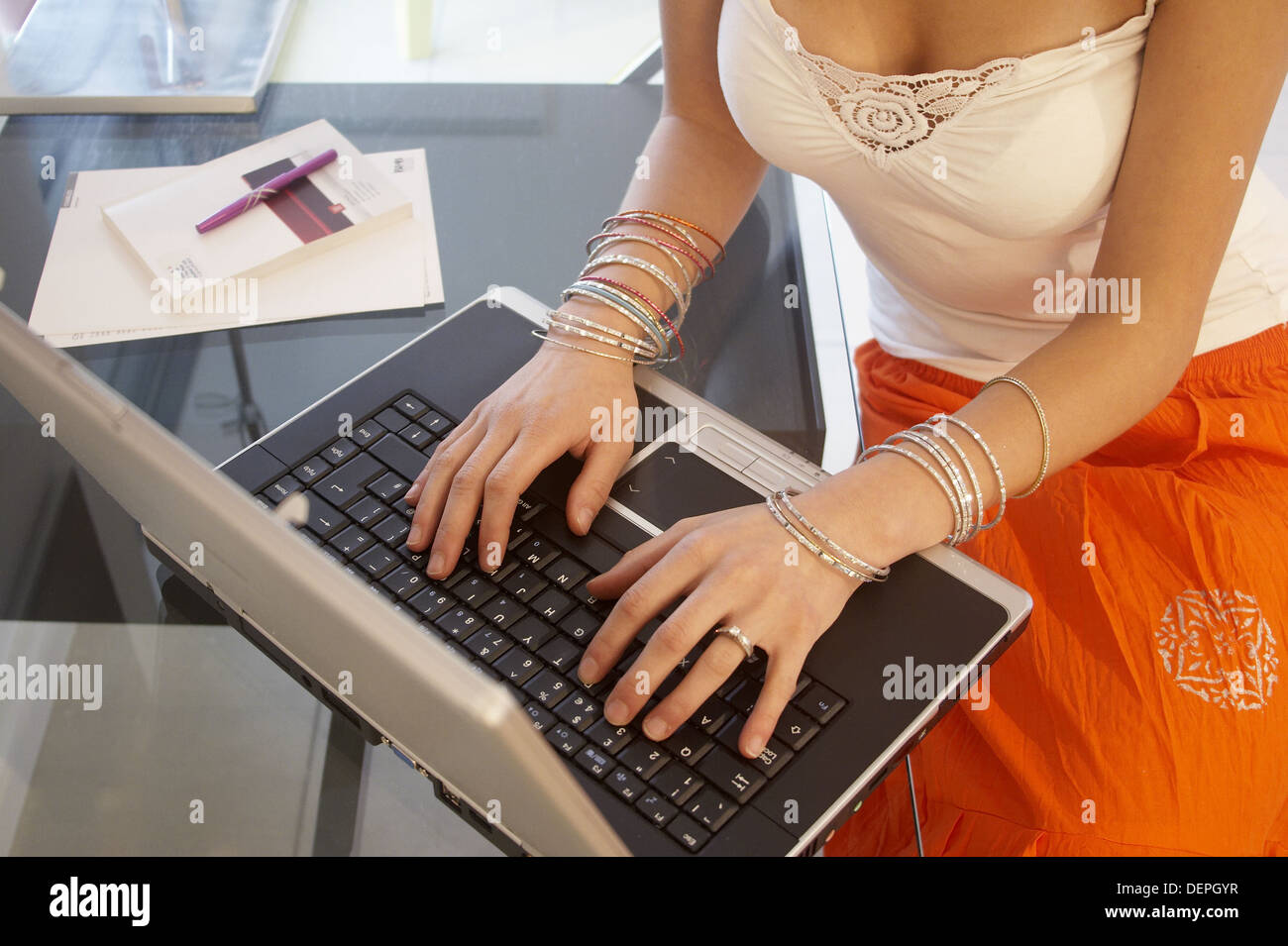 Closeup of girls hands on a laptop, wearing lots of bangles Stock ...