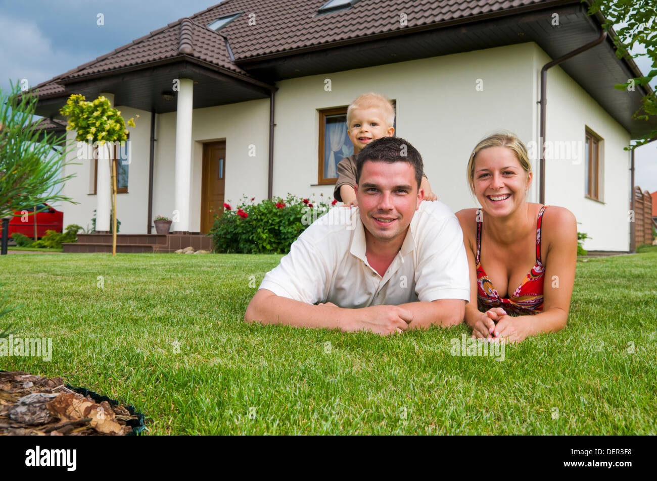 A happy family in front of their house in the garden Stock ...