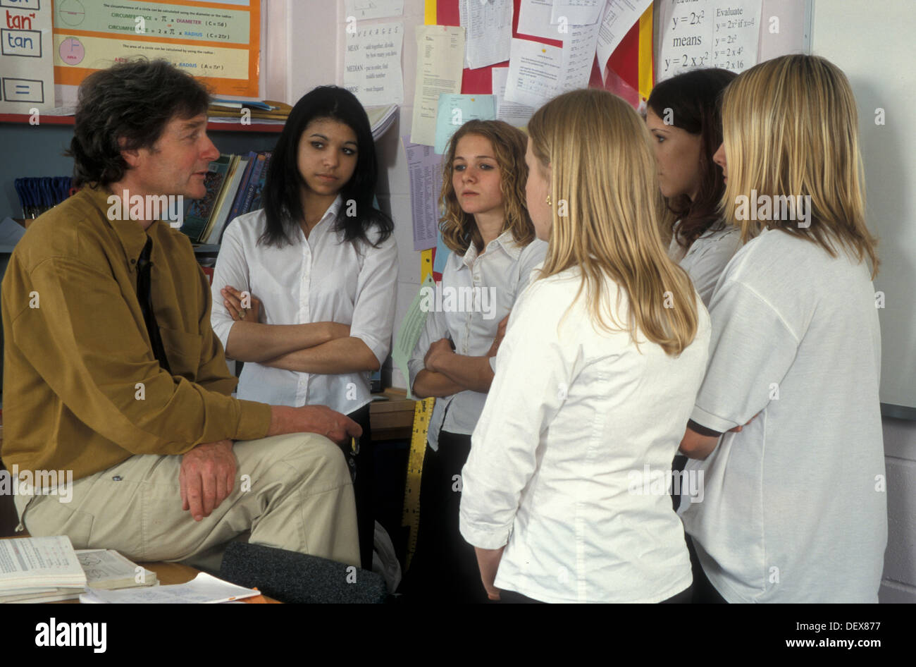 male teacher talking to group of teenage girls in classroom Stock ...