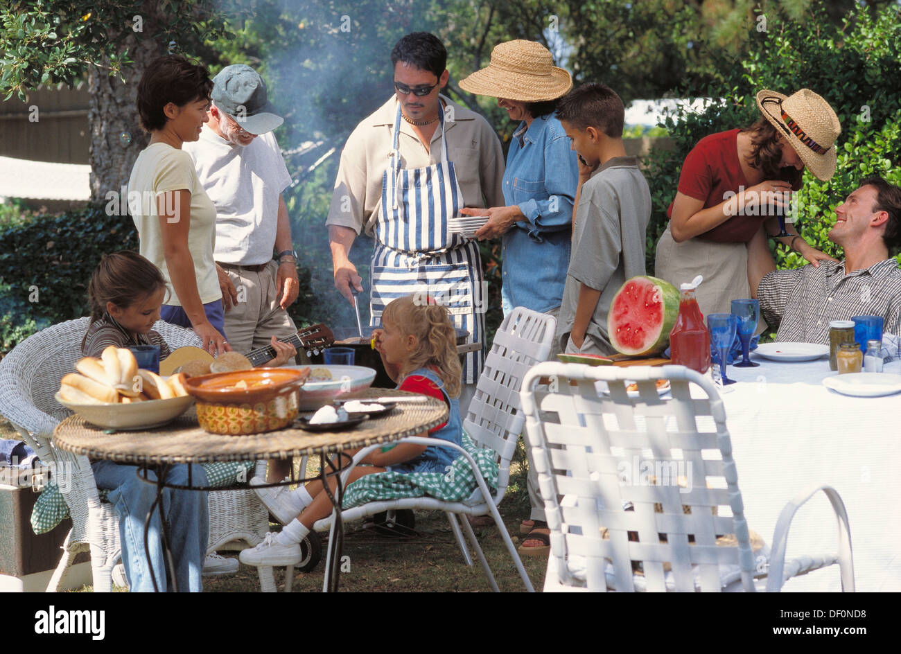 barbecue with family friends and neighbors in backyard stock