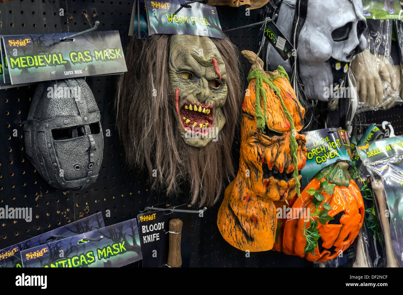 spooky scary halloween holiday masks of monsters demons and ghouls hanging on store display - Spooky Halloween Store