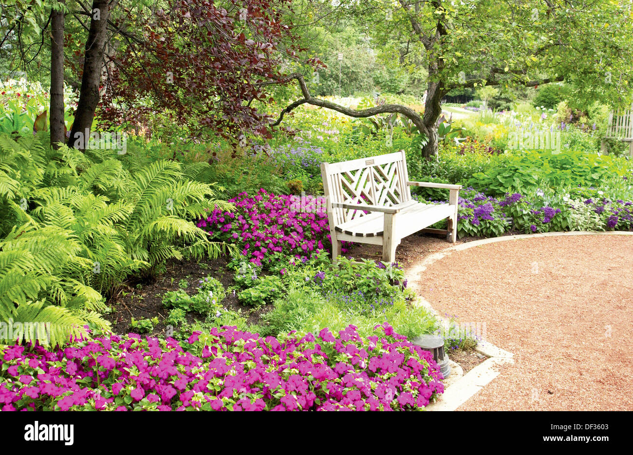 an empty park bench in the floral english gardens in the