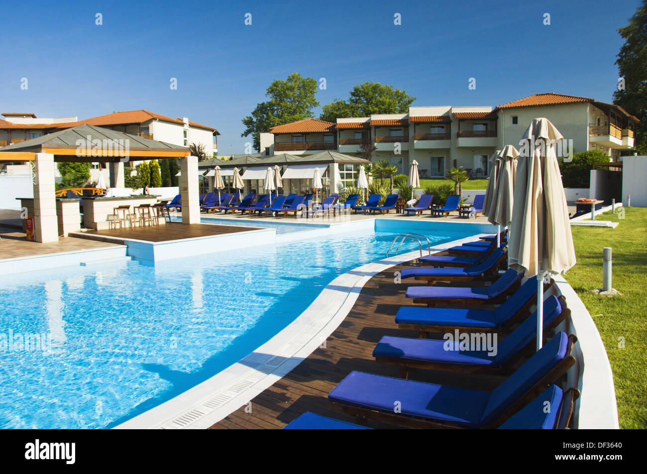 Pool Area With Blue Lounge Chairs At The Dion Palace Resort In Litohoro,  Greece