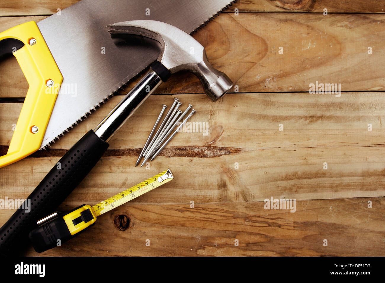 Hammer, nails, tape measure and saw on wood Stock Photo ...