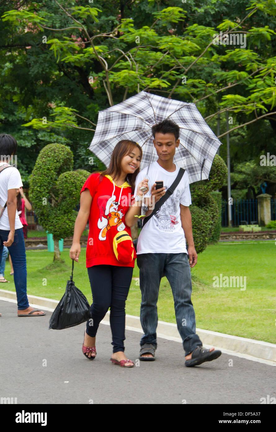 A burmese couple walk through mahabandoola garden park in - When you walk through the garden ...