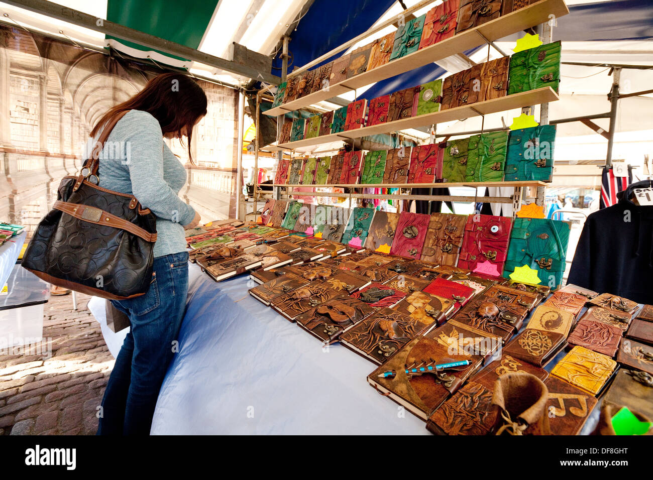 A woman shopping at a craft market stall buying books for Crafts for selling at market