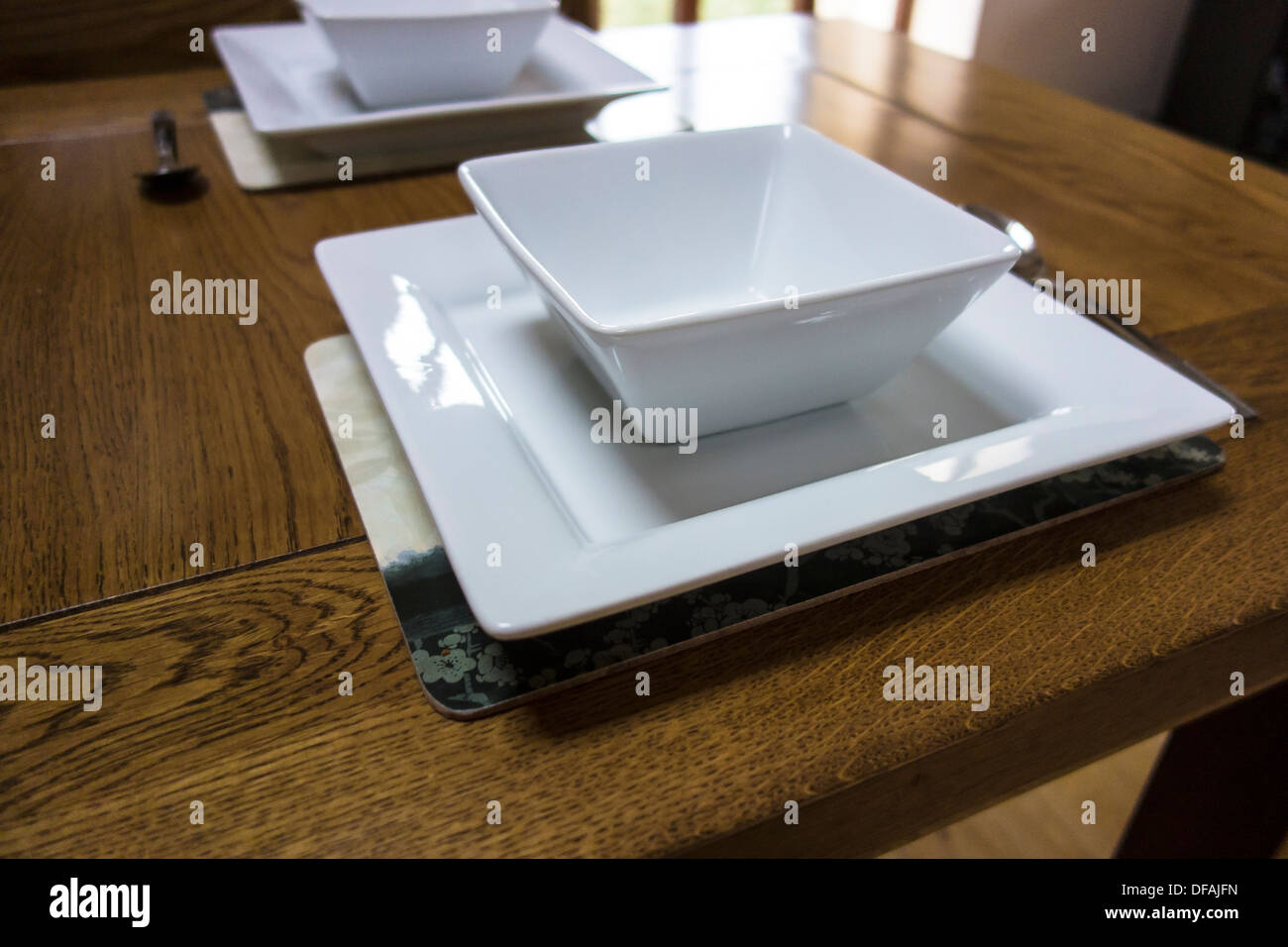 Square white bowls and plates & Place setting for two people.Square white bowls and plates Stock ...