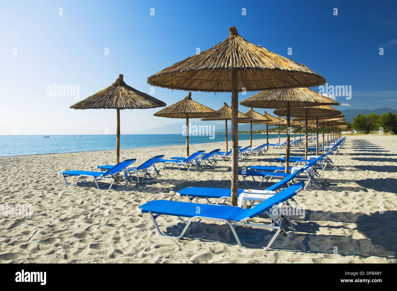 Thatched Roof Umbrellas And Blue Lounge Chairs On The Beach At The Dion  Palace Resort In Litohoro, Greece