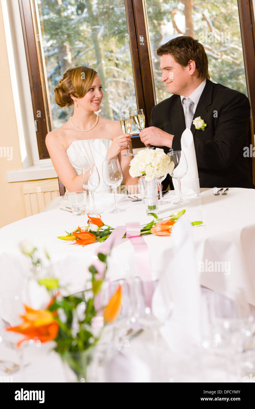 Happy Bride And Groom Toasting Champagne, Table Setting And Flowers  Foreground