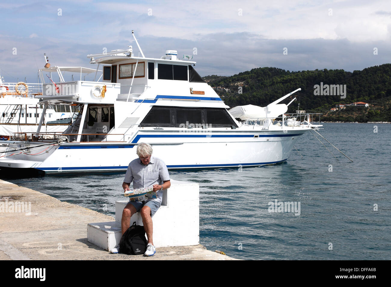 A tourist sits studying a map in front of boats moored in the New